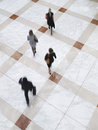 Blurred business people walking on tiled floor elevated view of Stock Photography