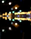 Blurred city at night bokeh background yellow and green spots on black reflection of colorful lights in water a lot of Stock Photography