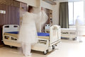 Blurred figure staff medical uniform fixing bed modern hospital room Royalty Free Stock Photo