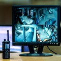 Blurred image on the monitor screen from four cameras by video surveillance. Workplace. CCTV. The policeman`s radio is nearby. Sq