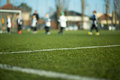Blurred kids playing soccer close up of field with children a match in the background Royalty Free Stock Photos