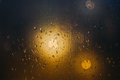 Blurred lights through steamy window with raindrops Royalty Free Stock Photo
