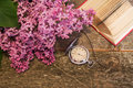 Blurred lilac branch on the background of the clock and an open Royalty Free Stock Photo