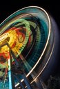 Blurred part of a Ferris wheel at night  with changing colors. Ride spinning, creating light streaks at night Royalty Free Stock Photo