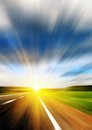 Blurred road and blue blurred sky with a shining sun Stock Image
