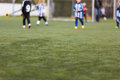 Blurred soccer pitch close up of artificial with players in the background Royalty Free Stock Photography