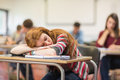 Blurred students in the classroom with one asleep girl young college sitting Royalty Free Stock Image