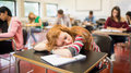 Blurred students in the classroom with one asleep girl young college sitting Stock Photo