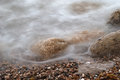Blurred surf and wet stones of sea coast Royalty Free Stock Photo