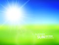 Blurry green field and blue sky with summer sun Royalty Free Stock Photo