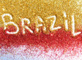 Blurry inscription Brazil on golden and red glitter sparkles on white background Royalty Free Stock Photo