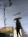 Blurry person under umbrella reflection shadow on rainy city street Royalty Free Stock Photo