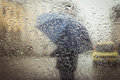 A blurry silhouette with umbrella on city street seen through wet window Stock Images