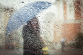 A blurry silhouette with umbrella of girl on city street seen through wet window Stock Photo