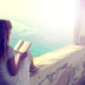 Blurry woman reading book relaxed blonde a outside light filter effect added Royalty Free Stock Image