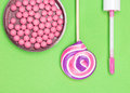 Blush and lip gloss on green background with lollipop