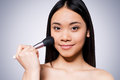 Blushing beauty beautiful young and shirtless asian woman holding make up brush on cheek and smiling while standing against grey Stock Image