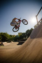 Bmx bike stunt bar spin rider performing a to a quarter pipe ramp on a skatepark Stock Image