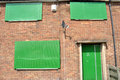 Boarded up council house a repossessed with green metal security shutters Royalty Free Stock Images