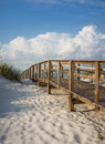 Boardwalk in the beach sand dunes inviting through on a beautiful early morning beautiful puffy clouds a clear blue sky Stock Images