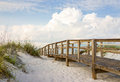 Boardwalk in the beach sand dunes inviting through on a beautiful early morning beautiful puffy clouds sky Stock Photo