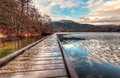 Boardwalk on lake with melting ice next to Royalty Free Stock Photo
