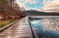 Boardwalk on lake with melting ice next to Royalty Free Stock Photo