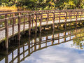 Boardwalk in nature reserve reflection of a raised crossing a pond a Royalty Free Stock Photography