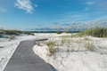 Boardwalk to pristine sunrise beach small rustic footpath through snow white sand dunes at a florida Royalty Free Stock Images
