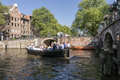 Boat in amsterdam the canals of amstedam the summer are full of life and tourists the green trees full of leaves and the flowers Royalty Free Stock Photography