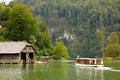 Boat approaching the pier konigssee germany timber boathouses or sheds by lake and a passenger Stock Photography