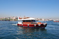 Boat on bosporus sea photo of red with istanbul cityscape golden horn bay istanbul turkey Royalty Free Stock Images