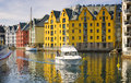 Boat and colorful buildings alesund norway a small glides through waters filled with reflections from in the waterway known as Royalty Free Stock Photography