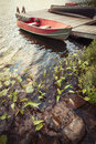 Boat at dock on small lake red wooden in cottage country with foreground of rocks and plants Royalty Free Stock Photography