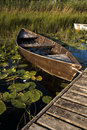 A boat at a dock among waterlilies