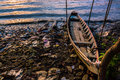 A boat and evening tide on messy riverbank at sunset Royalty Free Stock Photo