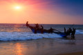 Boat and fishers on sunset background Stock Photos