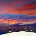 Boat fishing trolling at sunset rods and reels big game with in saltwater Stock Photography