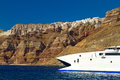 Boat at high volcanic cliff of Santorini island Royalty Free Stock Photos