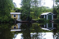 Boat house and summer cottage reflecting on lake Royalty Free Stock Photo