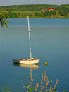 Boat on a lake mooring with her fore to buoy with cottages in background Stock Photo