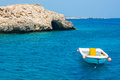 Boat near the rocky beach, view from the sea. Cyprus. Royalty Free Stock Photo
