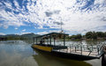 A boat park at noon little with white cloud in kanchanaburi river thailand Stock Photos