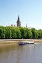 Boat at river in town gothic tower and cathedral roof behind blossoming chestnut trees embankment of with kaliningrad russia Stock Photo