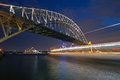 A boat streaks past the sydney harbor bridge frames view of downtown at twilight Stock Photo