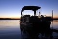 Boat at sunrise a silhouetted in the Stock Image