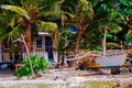 Boat on the tropical white sand beach in Asia in front of native house, Fishing boat parked in the sand Royalty Free Stock Photo