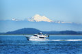 Boating on puget sound under mt baker a luxury cabin cruiser travels by mount washington the mountain is one of the snowiest Stock Photography