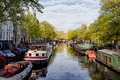 Boats on amsterdam canal houseboats in spring netherlands north holland province Stock Photography