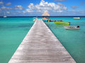 Boats attached to a pier and a thatched hut inside the tropical lagoon of the pacific atoll rangiroa an island of the tahiti Stock Photography